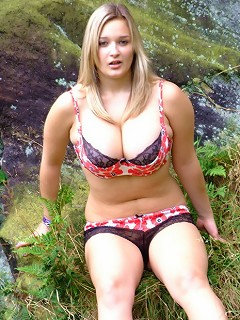 Busty British babe H Cup Holly teases and strips outdoors on the moors.